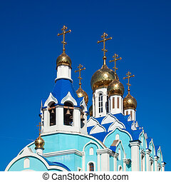 Cupolas of Russian orthodox church against blue sky.