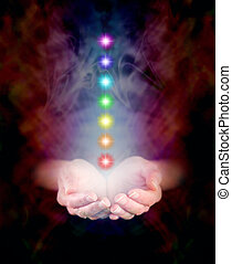 Cupped Hands and Chakras - Hands emerging from darkness,...