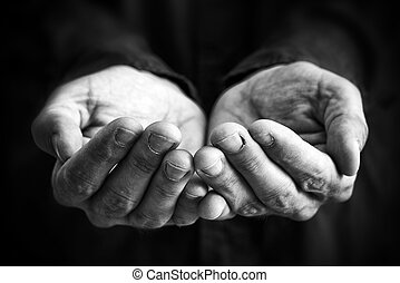 Cupped hands of a man hopefully held up. Cupped hands asking for something.