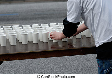 Cups - A volunteer at the marathon in Hamburg 2006, Germany.