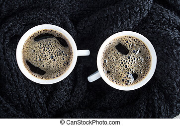 Cups of coffee and black woolen scarf