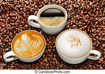 Cups of coffee on coffee beans