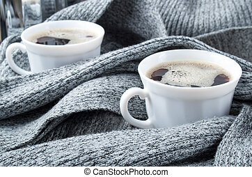 Cups of coffee wrapped in folds of gray woolen scarf