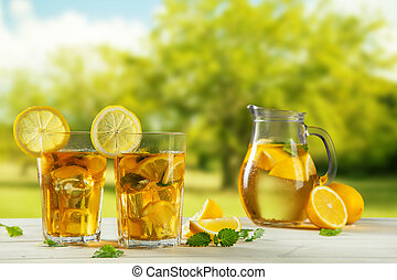 Cups of ice tea with trees on background - Two cups of ice...