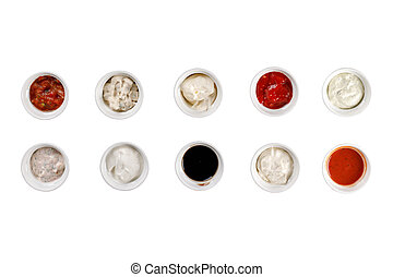 Cups with a variety of sauces on a white background.