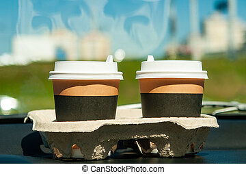 Cups with coffee on the car panel