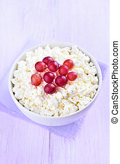 Curd cheese decorated with grapes in white bowl