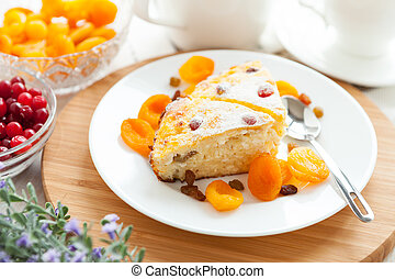 Curd pudding with dried apricot and raisins close-up on a plate