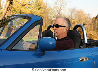 Cure For Mid-life Crisis - Middle-aged man driving a...