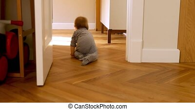 Curios child in bodysuit crawling from room - Back view of...
