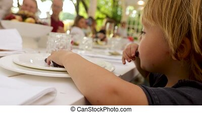Curios kid eating grapes at table in outside restaurant -...