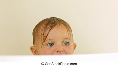 Curious adorable baby peeking out of bath - Charming kid...
