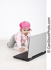 Curious baby  crawling to laptop