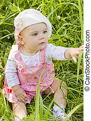 Curious baby girl on grass