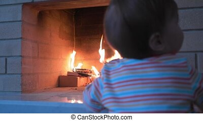 Curious baby girl passes by fireplace with fire. - Curious...