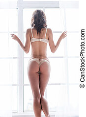 Curious beauty. Rear view of beautiful young woman in lingerie looking through the window