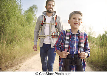 Curious boy hiking with his father