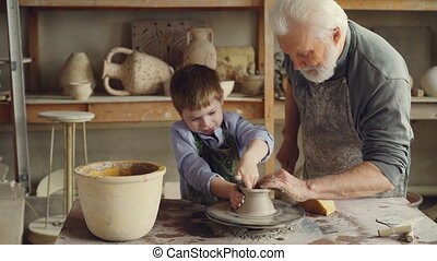 Curious boy is learning pottery from his experienced...