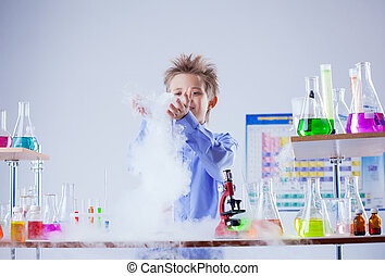 Curious boy watches chemical reaction of reagent, close-up