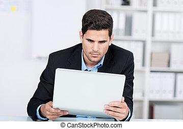 Curious Businessman Holding Laptop