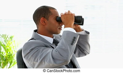 Curious businessman looking through binoculars in his office