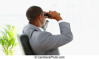 Curious businessman looking through binoculars in his office