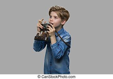 Curious caucasian boy using binoculars.