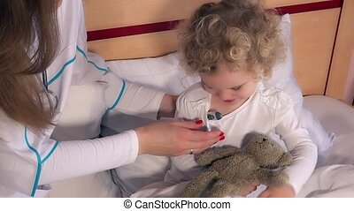 Curious child with woman doctor looking at thermometer after temperature measure