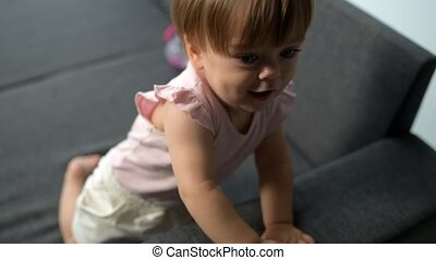 Curious cute toddler sitting on the sofa - Give it to me....