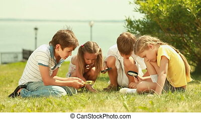 Curious explorers - Group of children with magnifying...