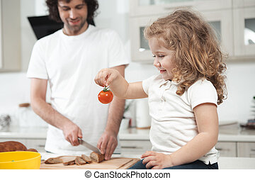 Curious female child staring at vegetable in kitchen