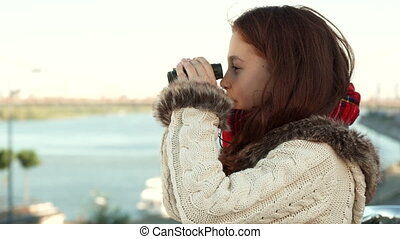 Curious girl is looking through binoculars