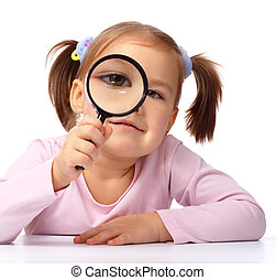 Curious little girl is looking through magnifying glass, isolated over white