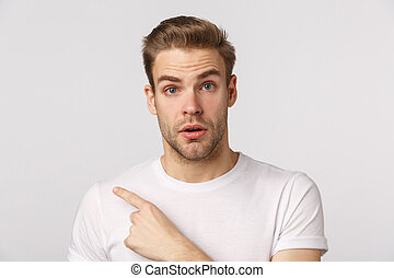 Curious guy consulting with shop assistant as pointing finger left at product. Attractive blond bearded man in white t-shirt looking interested, asking question, standing white background