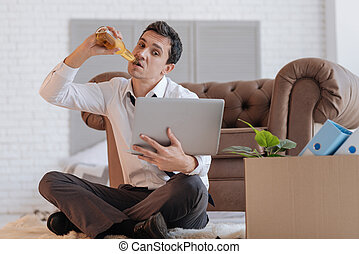 Curious jobless man drinking alcohol while browsing the Internet