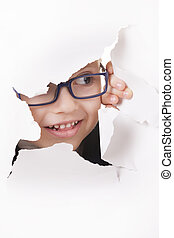 Curious kid in spectacles looks through a hole in white paper