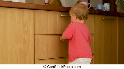Curious kid standing leaning kitchen drawer - Amazing cheeky...