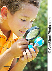 Portrait of cute schoolboy looking at small globe model through spy glass in natural environment