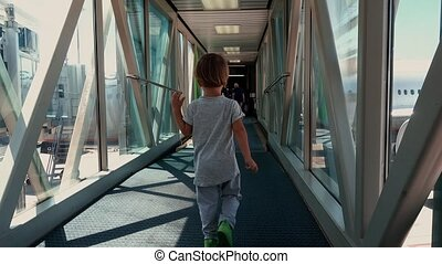 Curious little boy in glass long tunnel - Back view of small...