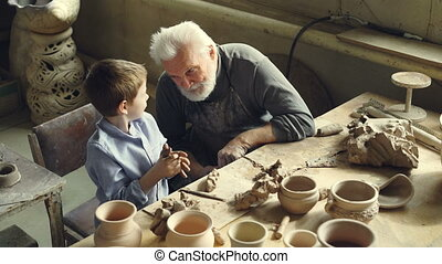 Curious little boy is kneading clay and talking to his...
