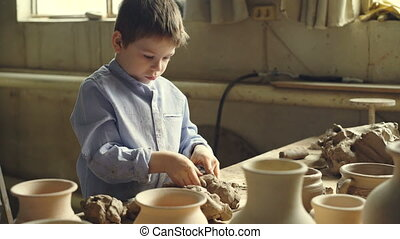 Curious little boy is playing with clay at working table in...