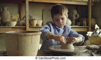Curious little boy is working with clay in his father's...