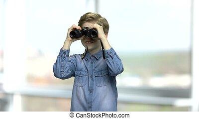 Curious little boy using binoculars.