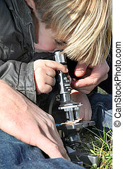 Curious little boy using microscope outdoors