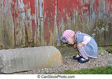 Little girl peeking in an old drainage pipe.