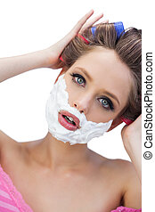 Curious model in hair curlers with shaving foam