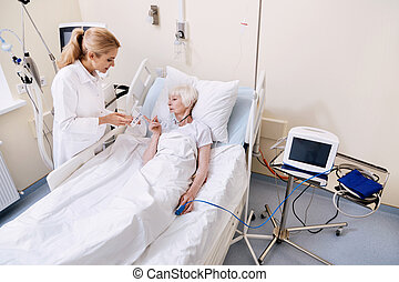 Curious neat aged woman asking her doctor for instructions