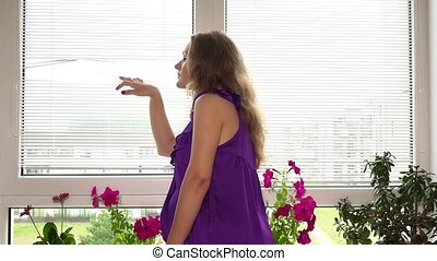 Curious pregnant woman looking through window blinds louver. Static shot