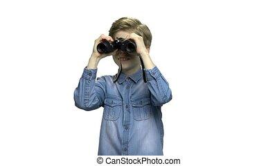 Curious preteen boy using binoculars. Cute caucasian boy in...