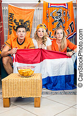 Curious Soccer Fans Watching Match At Home